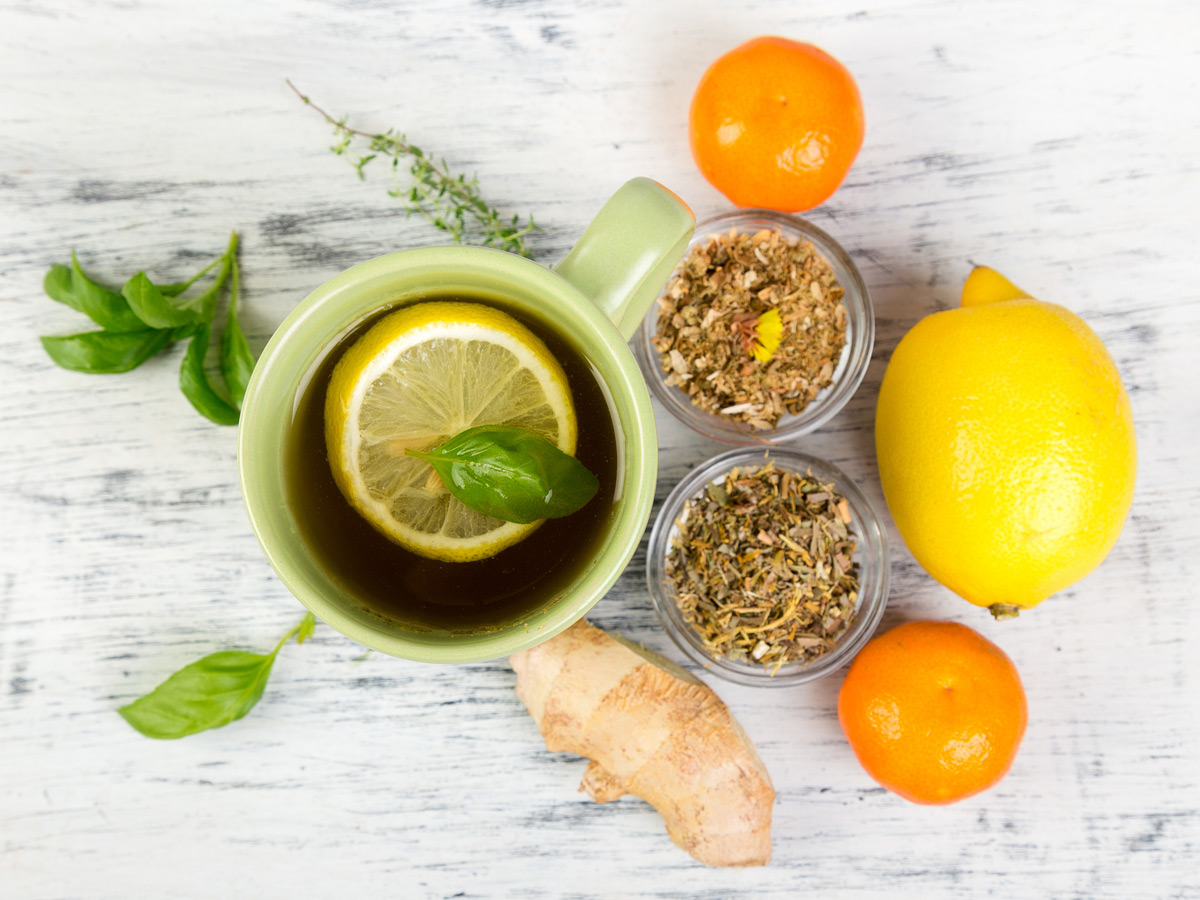 Common cold remedies of citrus fruits, ginger and herbal teas alongside a hot lemon and honey drink